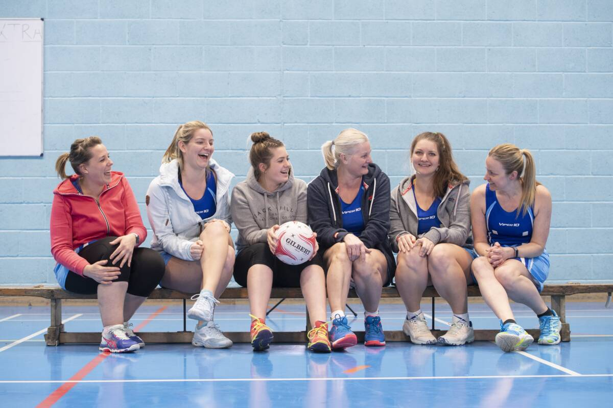 Selection of female netball players sat on a bench